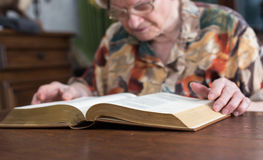 Old woman reading a book Stock Images