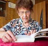 Old woman reading book at home Royalty Free Stock Photo