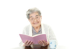 Old woman reading her book Stock Images