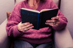 Old woman reading at home. Old woman reading a book at home Royalty Free Stock Photo
