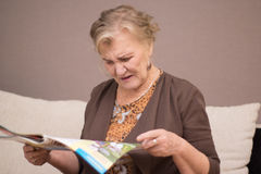 Old woman. Reading a magazine Royalty Free Stock Image