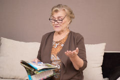 Old woman reading a magazine Stock Photography