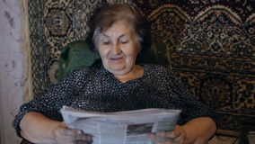Old woman reading newspaper at home