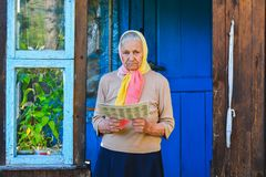 The old woman is reading the newspaper. royalty free stock image