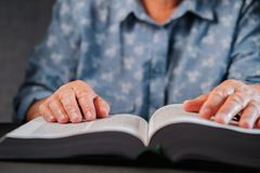 Old woman reading thick book at home. Grandmother with Bible. Concentrated elderly pensioner with wrinkles on hands. Attentively follows finger on paper page in stock photo