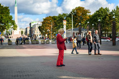 Old woman in red costume is reading map at central square of old town in Riga, Latvia Royalty Free Stock Photo