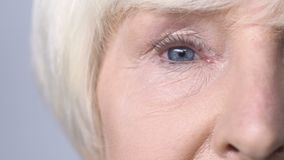 Old woman with red eyes looking into camera, allergy to cosmetics, lacrimation. Stock footage stock footage