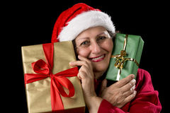 Old Woman in Red with Two Wrapped Christmas Gifts. Smiling gentle woman with Santa Claus cap and red coat. She is holding a golden and a green wrapped Christmas Royalty Free Stock Photography