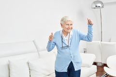 Old woman rejoices with vitality and joie de vivre. Old woman rejoices in vitality and joie de vivre and keeps her fingers crossed Royalty Free Stock Image