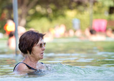 Old woman resting in pool. Old woman enjoying bathing in outdoor swimming pool with hot water in summertime Stock Photo