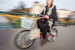 Old woman riding a bicycle around the city Stock Images