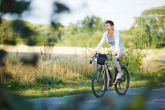 Old woman riding her bike Royalty Free Stock Photography