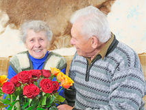Old woman with roses. And old man sit near her Royalty Free Stock Photo