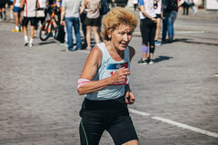 Old woman runner competes Stock Photos