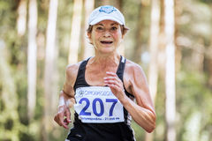 Old woman runs through forest and smiling. Chelyabinsk, Russia -  July 9, 2016: old woman runs through forest and smiling during Summer half marathon Royalty Free Stock Image