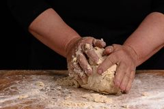 An old woman's grandmother is kneading a dough for cooking bread. An old woman's grandmother is kneading a dough for the preparation of bread on a black Stock Image