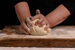 An old woman's grandmother is kneading a dough for cooking bread. An old woman's grandmother is kneading a dough for the preparation of bread on a black Stock Photography