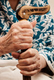 Old woman's hand holding a stick. Old woman's hands are based on a vertical stick Royalty Free Stock Photography