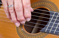 Old woman's hand playing guitar Stock Photography