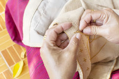 Old woman`s hand to picth brown yarn in to clothes Stock Photo