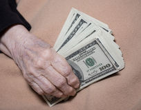 Old woman`s hands holding dollars Stock Image