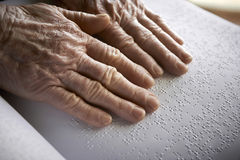 Old woman's hands, reading a book with braille language Stock Photography