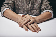 Old woman's hands resting on grey surface Royalty Free Stock Photos