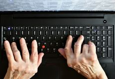 Old woman`s hands typing on laptop. Keyboard royalty free stock images