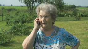 Old woman 80s tells on the mobile phone stock video footage