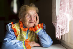 Old woman sadly looking out the window. Royalty Free Stock Photo