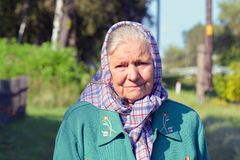 An old woman in a scarf. Portrait of a lonely old woman standing in a village. An old woman in a scarf. Portrait of a lonely elderly woman standing in a village Royalty Free Stock Photos