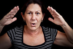 Old woman screaming. Portrait of an old woman screaming and gesturing with her hands isolated on a black background Stock Photos