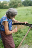 Old woman with the scythe. Cutting grass Royalty Free Stock Photo