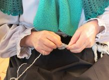 Old woman seamstress working with wool jerseys irons Stock Photo