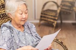 Old woman seated reading carefully a document or terms of a insu. Rance. Old obaasan grandma, japanese descendant Royalty Free Stock Photography