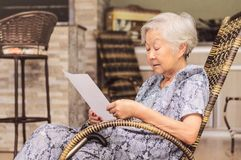 Old woman seated reading carefully a document or terms of a insu. Rance. Old obaasan grandma, japanese descendant Royalty Free Stock Image