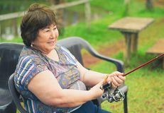 Old woman seated, smiling, fishing, holding a fishing rod. B Stock Photography