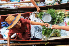 Old woman selling fruits and vegetables in a traditional floating market Stock Photography