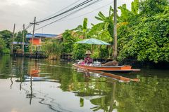 Old woman sells food from her boat in the canals of Nonthaburi. Nonthaburi, Thailand - March 31, 2018 : Old woman sells food from her boat in the canals of Stock Images