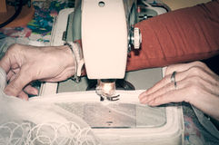 Old woman sewing wedding dress on vintage sewing machine. Stock Photo