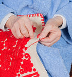 Old woman sews. Old woman sitting on the bed, and sewing Stock Images