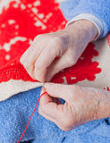 Old woman sews. Old woman sitting on the bed, and sewing Royalty Free Stock Photo