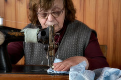 The old woman sews. On the sewing machine Royalty Free Stock Images