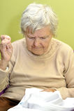 Old woman sews clothes. Royalty Free Stock Photos