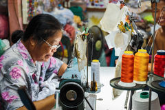 Old  woman sews on the sewing machine in the street Stock Photo