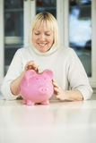 Old woman showing piggybank and euro coin Royalty Free Stock Images