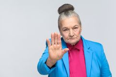 Old woman showing stop sign at camera. Aged grandma showing stop sign at camera. expressive grandmother with light blue suit and pink shirt standing with royalty free stock photos