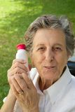 An old woman shows the product she is satisfied with. An old woman between 70 and 80 years old is demonstrating the natural product she is satisfied with. The Royalty Free Stock Image