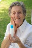 An old woman shows the product she is satisfied with. An old woman between 70 and 80 years old is demonstrating the natural product she is satisfied with. The Stock Image