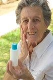 An old woman shows the product she is satisfied with. An old woman between 70 and 80 years old is demonstrating the natural product she is satisfied with. The Stock Images